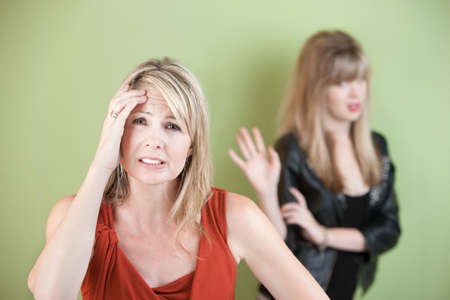 Upset mom with frustrated daughter over green background photo