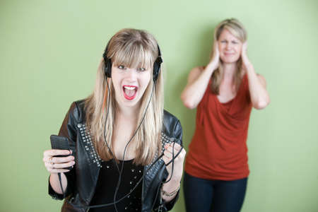 adult 80s: Excited retro-styled woman sings out loud with annoyed mom behind her Stock Photo