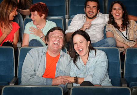 Groups of friends in the audience laugh and smile photo