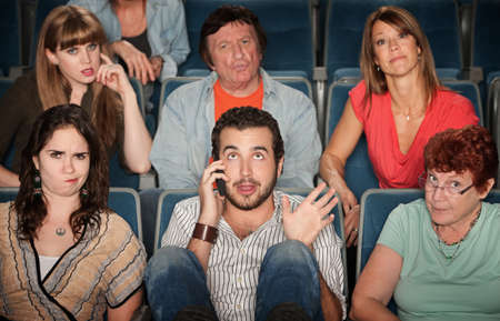 disrespectful: Young man on phone disturbs people in theater Stock Photo
