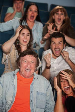 agachado: Grupo de los siete hombres y las mujeres reaccionan horrorizados Foto de archivo