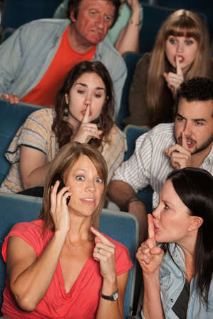 shush: Loud woman on phone annoys people in theater Stock Photo