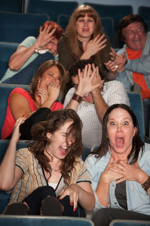 gross: Group of seven scared audience members cringe in their seats Stock Photo
