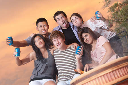goofy: Group of six friends with beverage cans make funny faces Stock Photo