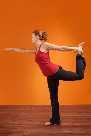 Young Caucasian woman practising yoga stretches her leg Stock Photo - 12364886