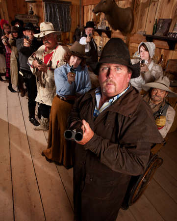 The entire saloon points their guns at an unseen danger. photo