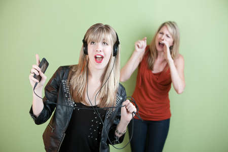 loud: Teen singing out loud with frustrated mom behind her Stock Photo