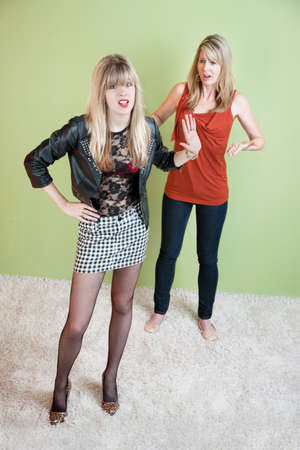 rebellious: Embarrassed mother with daughter in revealing clothing Stock Photo