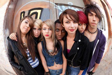 de maras: J�venes punks adolescentes posan para una foto de grupo serio detr�s de un edificio abandonado. Foto de archivo