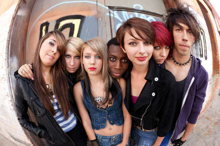 navel piercing: Young teen punks pose for a serious group photo behind an abandoned building.