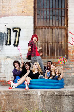 Crazy teen punks sit together in an inflatable pool behind an old warehouse downtown. photo