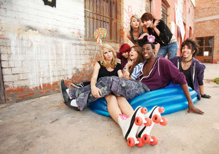 Young teens happily hang out and play with an inflatable pool behind an abandoned building. photo