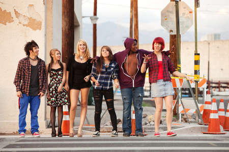 Young and happy gang of teen punks cross the street together. photo