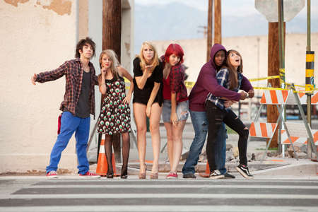 A group of young, fun-loving, punky looking teens pose for a group photo. photo