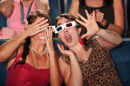 gradas estadio: Dos mujeres asombrados con gafas 3D reaccionar ante una película