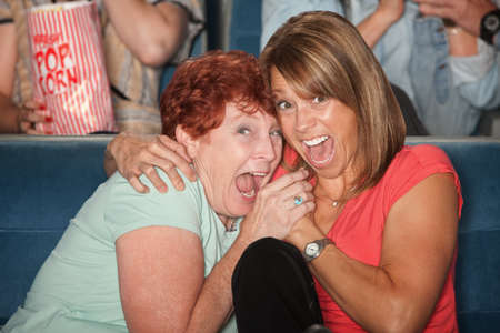 curledup: Two scared women scream out loud in fear at theater Stock Photo
