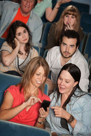 Two women talking in theater with annoyed audience photo