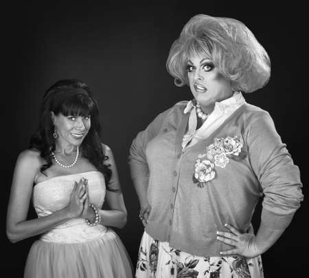 disgusted: Innocent woman and disgusted drag queen over red background Stock Photo