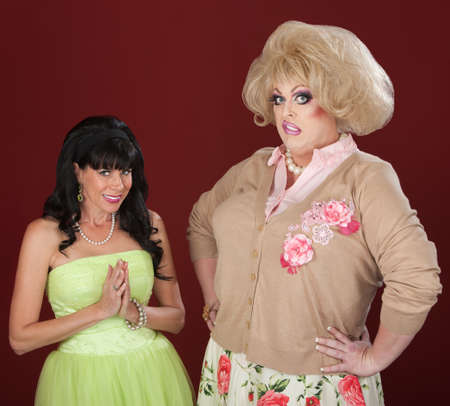 Innocent woman and disgusted drag queen over red background Banque d'images