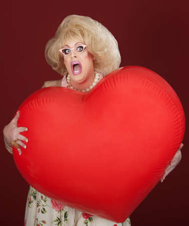 Emotional drag queen holds large red heart