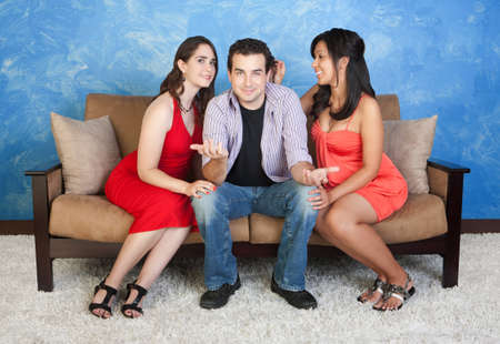 pimp: Two women flirting with a handsome man on sofa Stock Photo
