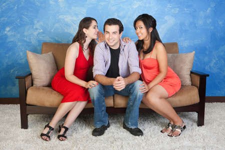 polygamy: Two pretty women whisper and flirt with handsome man Stock Photo