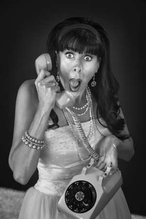 Shocked retro-styled woman holding telephone over maroon background Stock Photo - 12365057