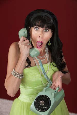 chitchat: Shocked retro-styled woman holding telephone over maroon background