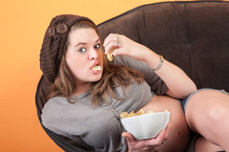 woman on couch: Pretty pregnant woman resting on couch eats potato chips