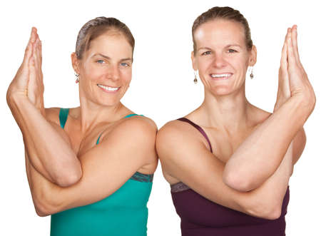 Two women perfrom namaskar with hands twisted Stock Photo - 12365021