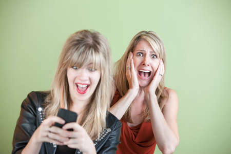 alarmed: Excited daughter texting with shocked mom behind her over green background