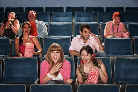 Group of seven people laughing out loud in a theater photo