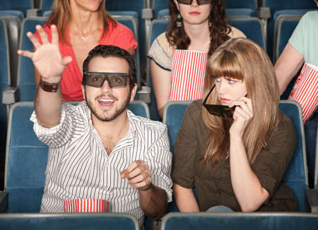 Annoyed girl with date reaching out with 3D glasses Stock Photo - 12365123