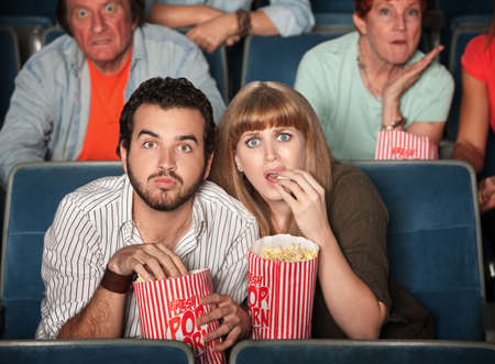 Scared Caucasian couple eating popcorn in theater  Stock Photo - 12365056