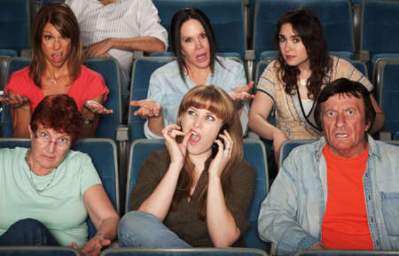 Frustrated audience with rude woman on phone photo