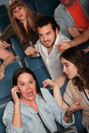 molesto: Una mujer fuerte en el teléfono público frustra en el teatro Foto de archivo