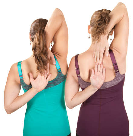 Two women stretching shoulders over white background photo