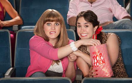 suspenso: Dos mujeres ansiosas disfrutar de películas con una bolsa de palomitas de maíz