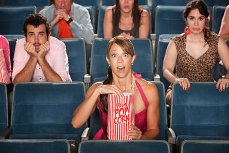 spectator: Surprised people with eyes wide open in theater