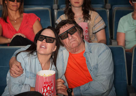 Loving couple in movie theater with 3D glasses 新聞圖片