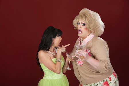 Woman and drag queen holding martinis arguing Stock Photo - 12638333