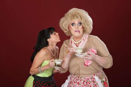 Vrouw met kopje thee probeert te kussen geschokte drag queen