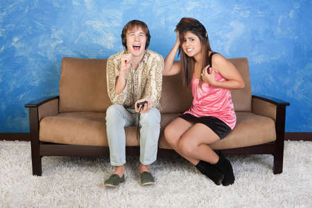 teenagers laughing: Laughing young man with headphones with distraught girl