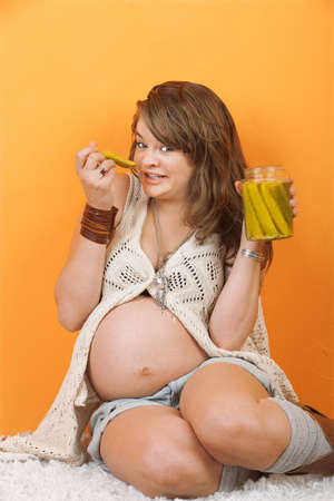 Caucasian pregnant woman sitting on the floor eating pickles Stock Photo - 12638337