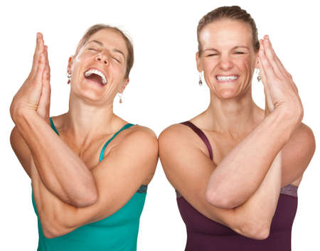 Two laughing women performing entwined namaskar over white background