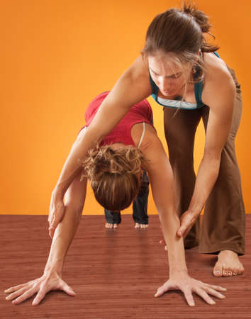 Yoga instructor helping student perform Adho Mukha Svanasana posture over orange background