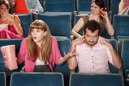 Frustrated young woman with mean boyfriend in theater Stock Photo - 12640860
