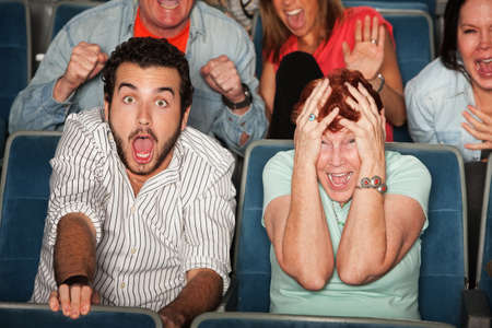 suspense: Group of frightened people in a theater