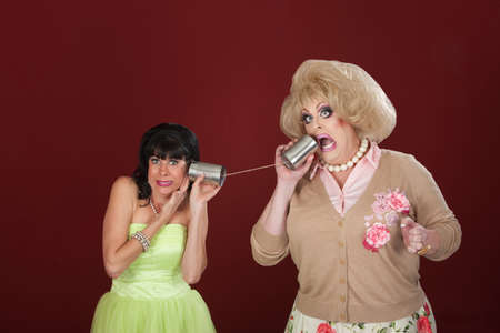 tin can phone: Drag queen yells into tin can phone to pretty woman