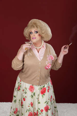 Drag queen holding cigarette and martini over maroon background 스톡 콘텐츠